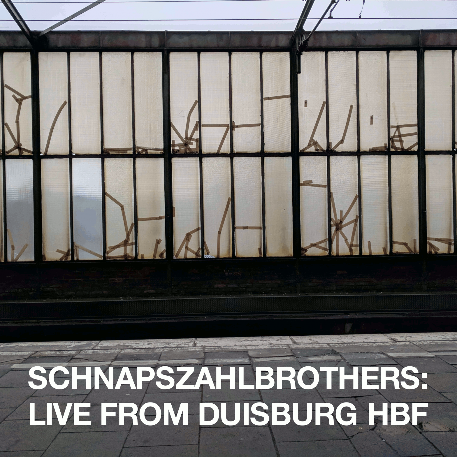 EIne schmutzige Bahnhofshallenwand. Aufschrift: Schnapszahlbrothers: Live from Duisburg Hbf