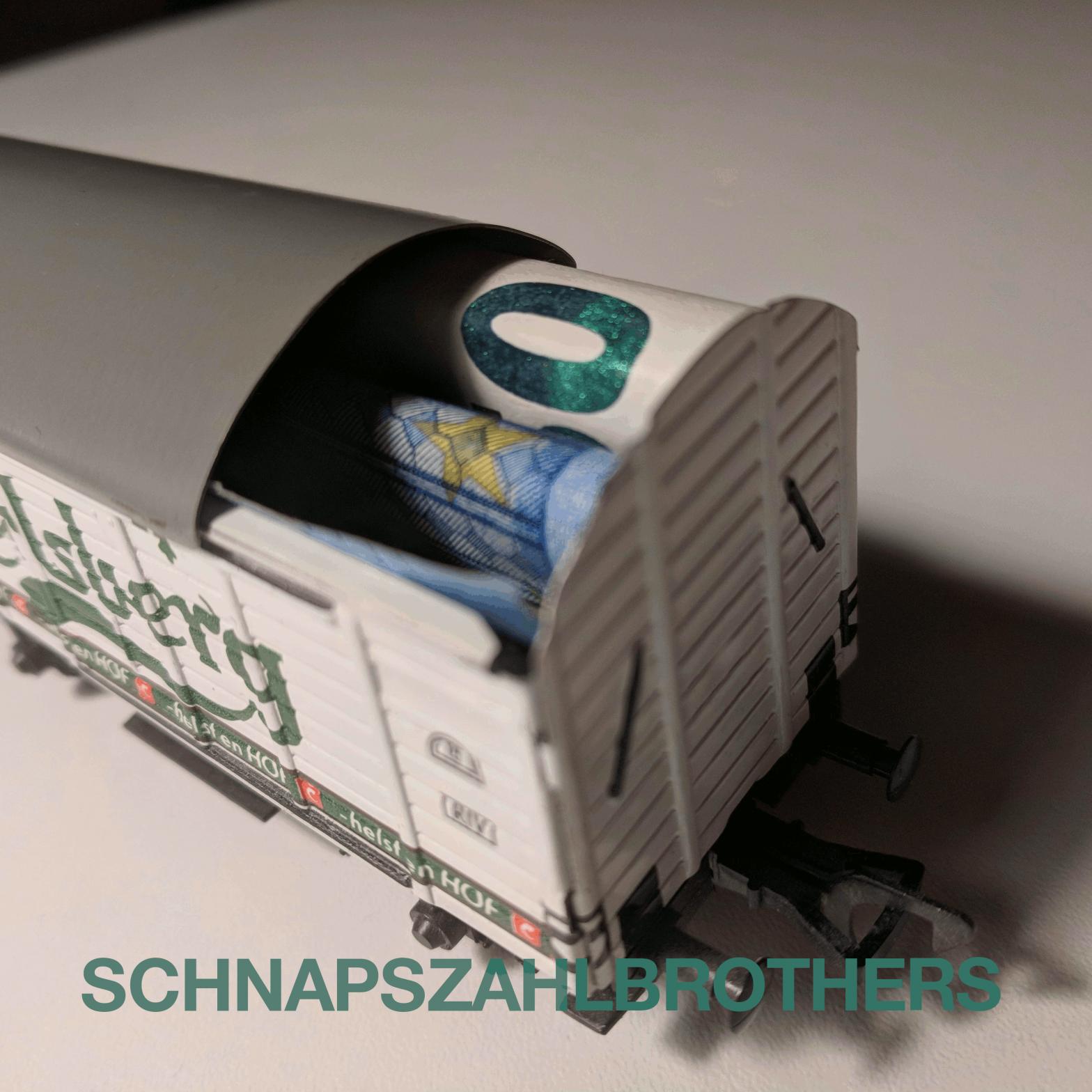 Ein Modellbahnwagen (Spurweite H0) mit Carlsberg-Bierwerbung. Das Dach ist beiseitegeschoben und ein 20 Euro-Schein lugt heraus.